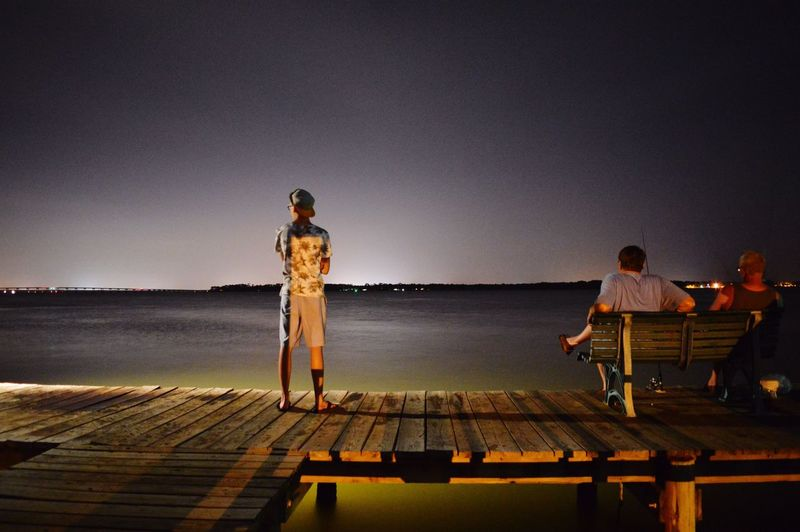 Rear View Of People On Pier At Night