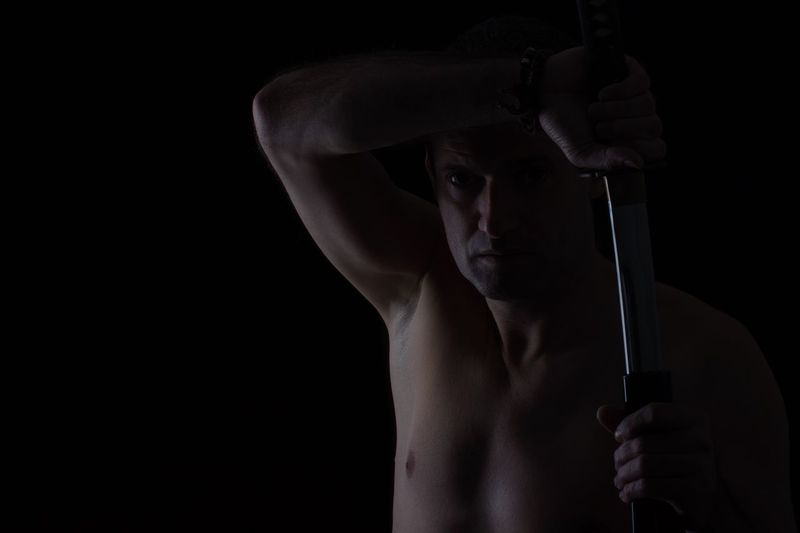Close-Up Of Shirtless Man Holding Sword Against Black Background