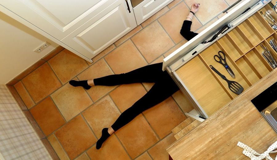 Low Section Of Person Lying Down On Floor In Kitchen