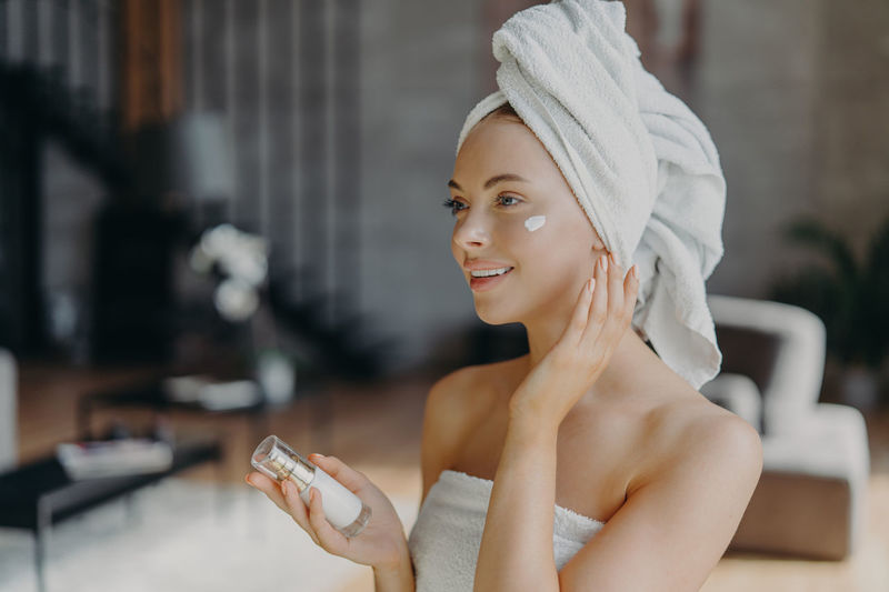 Smiling young woman applying moisturizer at home