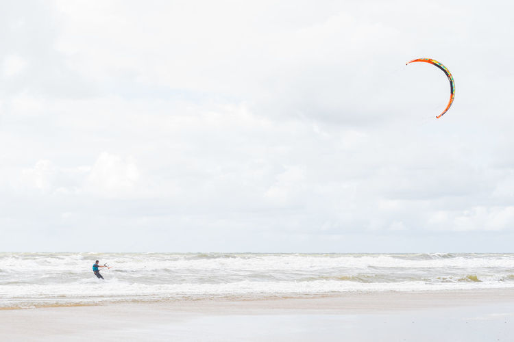 Man kiteboarding in sea against sky