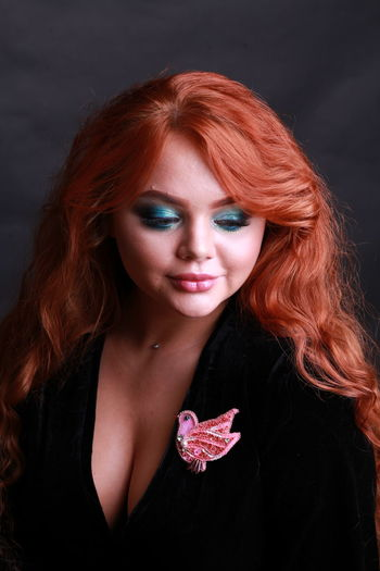 Beautiful woman with redhead looking away against black background
