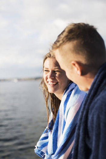 Portrait of smiling man and woman in water
