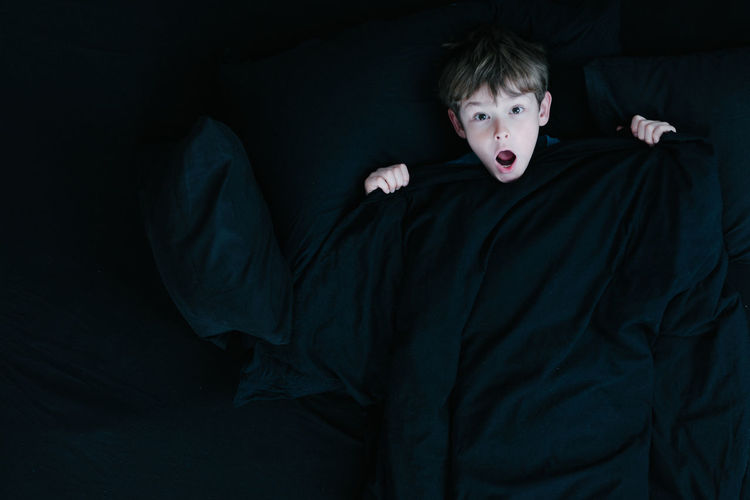 Boy in awe, surrounded by black bed cover and sheets Awe Bed Black Black Background Child Children Only Cover Dark Dark Face Horror Mission Night One Boy Only One Person People Portrait Shadow Sheets Shock Spooky Surprise Welcome To Black