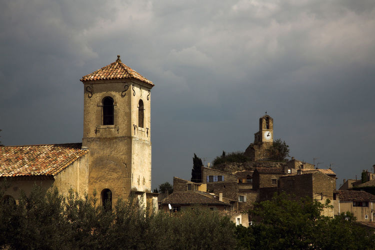 Stormy weather and dramatic sky over the old village of Lourmarin, in Provence, France Church Dark Clouds Provence Stormy Weather Architecture Building Building Exterior Built Structure Clock Tower Cloud - Sky Day History No People Old Houses Outdoors Place Of Worship Sky Spirituality Stormy Stormy Sky Temple The Past Tower Village Village View