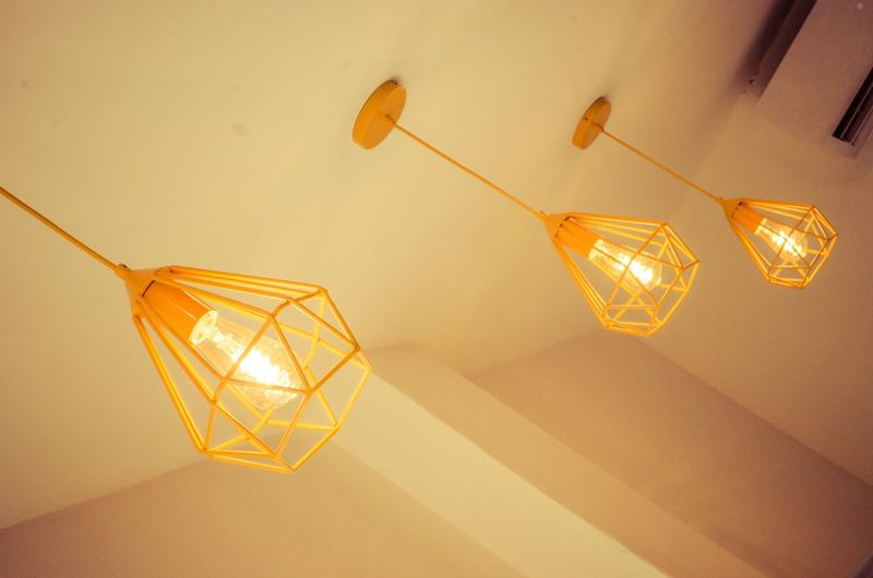 High angle view of illuminated light bulbs hanging from ceiling
