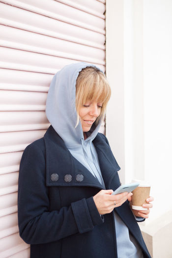 Woman in hood using mobile phone while standing outdoors