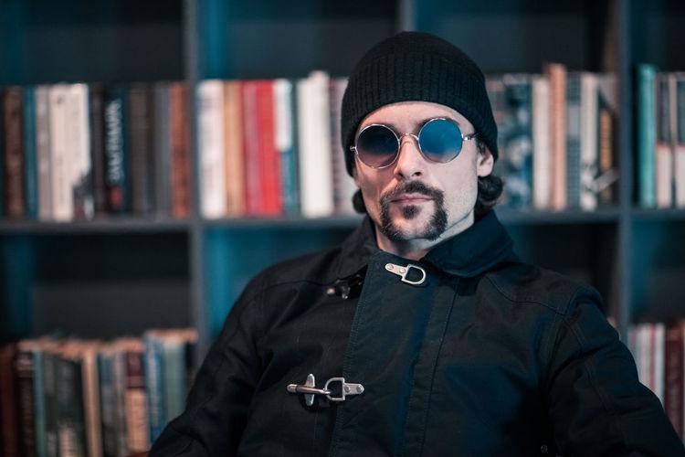 Portrait of handsome man wearing sunglasses while sitting against bookshelf