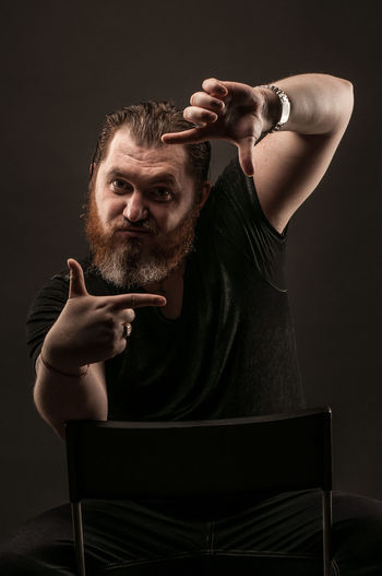 Adult Arms Raised Beard Black Background Body Part Casual Clothing Dark Emotion Facial Hair Front View Hairstyle Human Arm Human Body Part Human Face Human Limb Indoors  Looking At Camera Men Mid Adult One Person Portrait Studio Shot Young Adult
