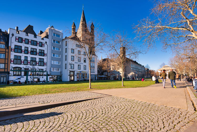 Cologne, GERMANY - February 15, 2019: Unidentified pedestrants enjoy the warm winter sun at the historic Rhein promenade of Cologne Architecture Building Exterior Built Structure Building City Tree Cobblestone Nature Sky Incidental People Footpath History Travel Destinations The Past Plant Street Day Clear Sky Residential District Travel Outdoors Paving Stone