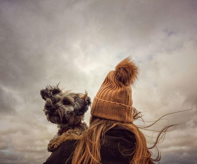 A rear view of a Fashionable young girl in a warm woollen, knit hat and coat holding her scruffy pet dog over her shoulder as the wind blows her hair with dark stormy clouds above. Domestic Animals Sky Pets Rear View Cloud - Sky Real People Dog Outdoors Wind Windy Windy Day Girl Autumn Winter Autumn Collection Wooly Hat Fashion Hug Hair Blowing Lifestyles Storm Stormy Weather Friendship Coat Second Acts Perspectives On Nature Be. Ready. Be. Ready.