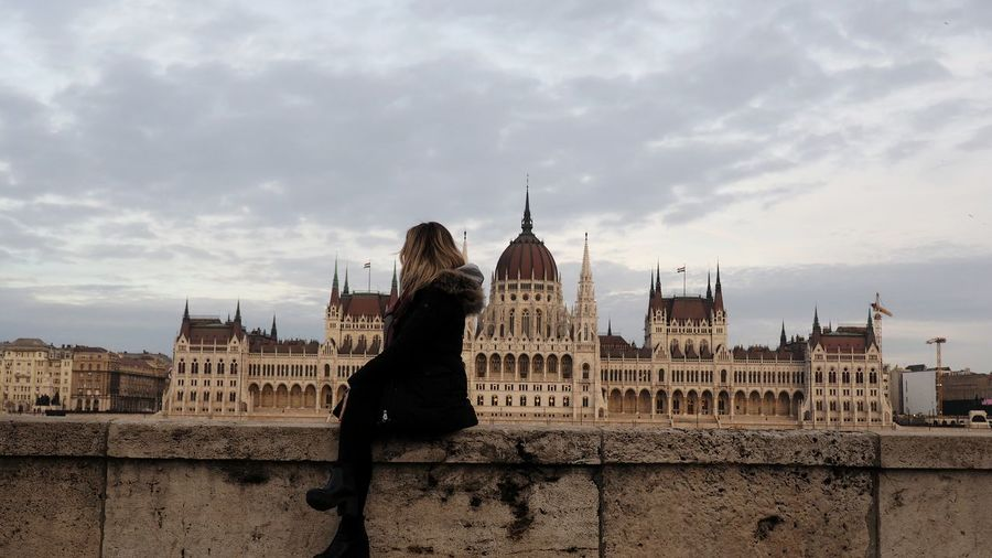 Woman Sitting On Retaining Wall Against Hungarian Parliament Building
