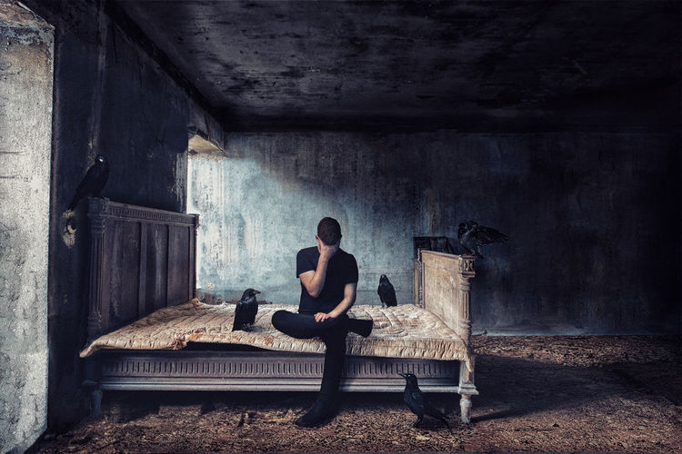 Woman sitting on chair in abandoned room