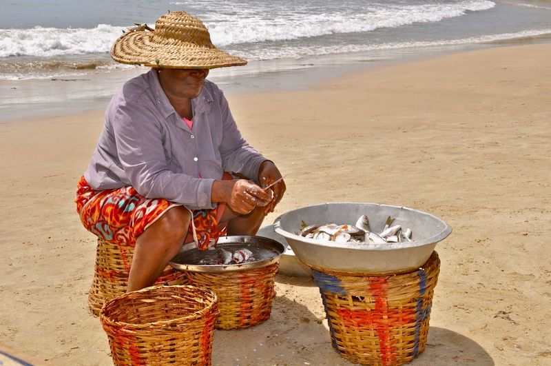 Woman cleaning fish while sitting on beach