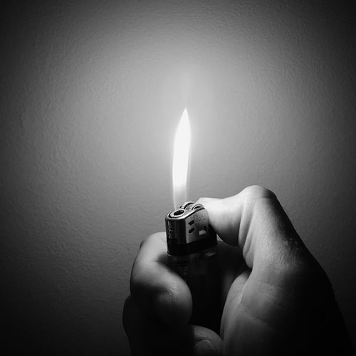 Cropped Hand Igniting Cigarette Lighter Against Wall
