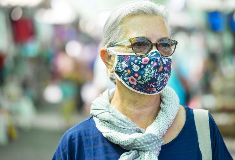 Senior woman wearing flu mask looking away while standing outdoors