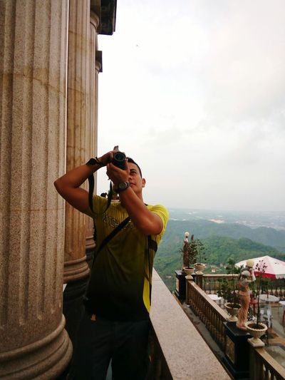 Young man photographing through digital camera by column against sky