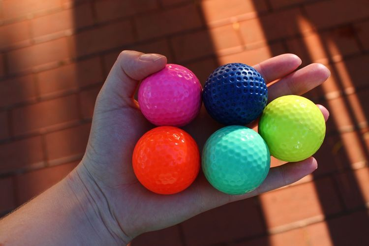 Cropped Hand Of Woman Holding Colorful Golf Balls Over Floor