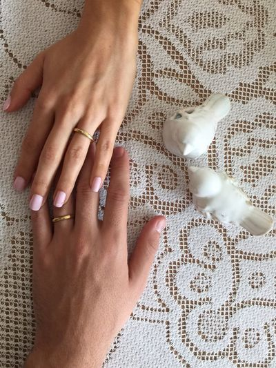 High angle view of couple hands wearing engagement rings on table