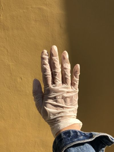 Cropped hand of woman wearing glove against wall
