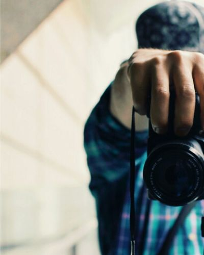 Cropped image of man holding digital camera
