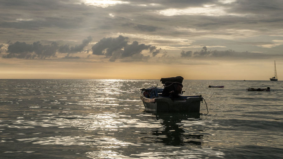Motorboat moored on sea against cloudy sky during sunset