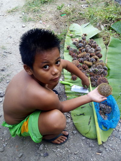 Portrait of boy holding fruit while crouching on ground
