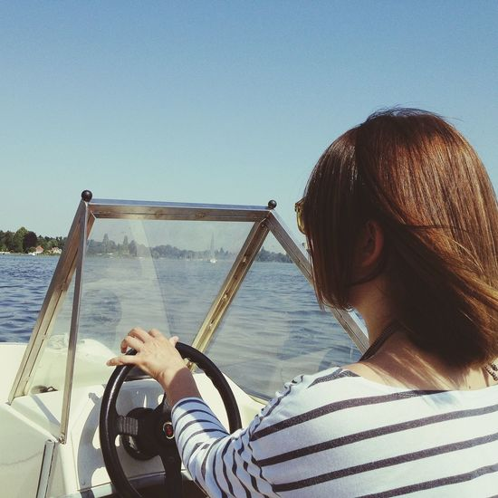 Rear view of young woman driving speedboat