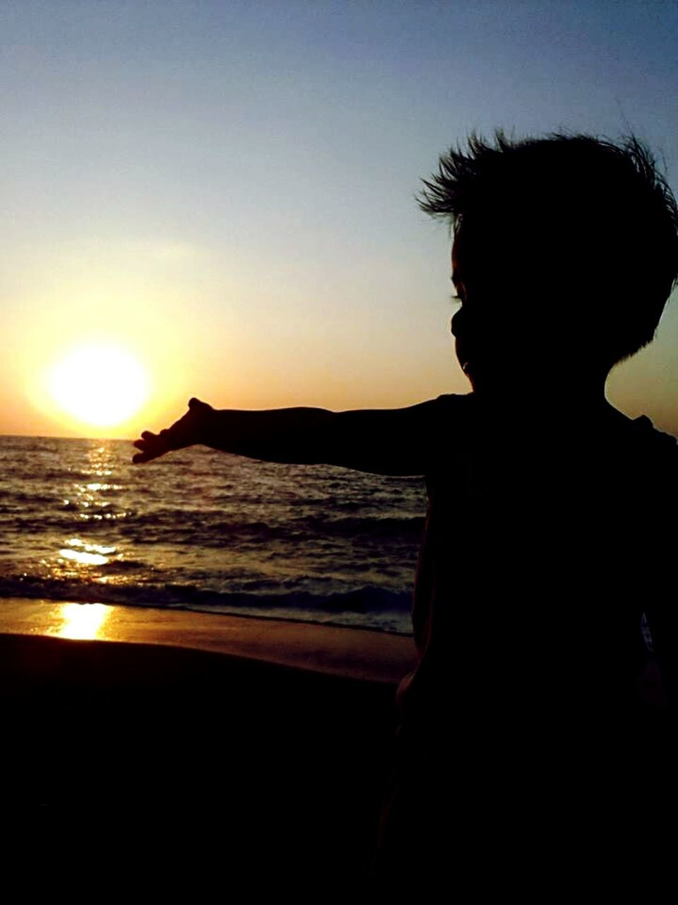 sunset, silhouette, sun, one person, sea, nature, real people, leisure activity, water, outdoors, lifestyles, scenics, beauty in nature, standing, sky, clear sky, day, people