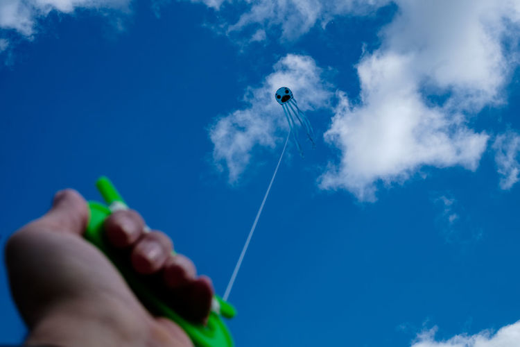 Low angle view of hand flying kite against blue sky