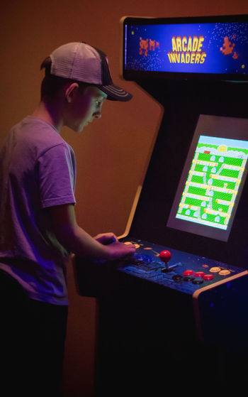 Indoors  Technology Side View One Person Casual Clothing Arts Culture And Entertainment Real People Cap Playing Three Quarter Length Waist Up Illuminated Standing Looking Computer Leisure Activity Men Music Young Men Screen Arcade Games Arcade Teenager Childhood Child Videogames Player