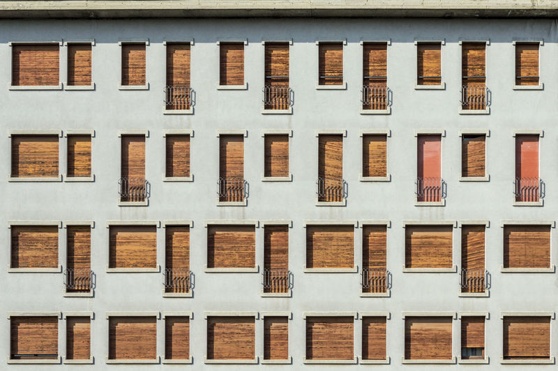 Concrete facade with series of facade of windows and small balconies Architecture Backgrounds Brown Building Building Exterior Built Structure City Day Full Frame In A Row Low Angle View No People Outdoors Pattern Repetition Residential District Side By Side White Color Window Wood - Material