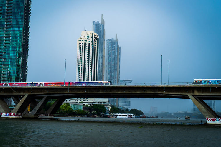 The train crosses the Chao Phraya River. Built Structure Architecture Building Exterior Office Building Exterior City Connection Bridge Skyscraper Water Sky Building Bridge - Man Made Structure Modern Transportation Tall - High Waterfront River Nature Travel Destinations No People Cityscape Outdoors Financial District
