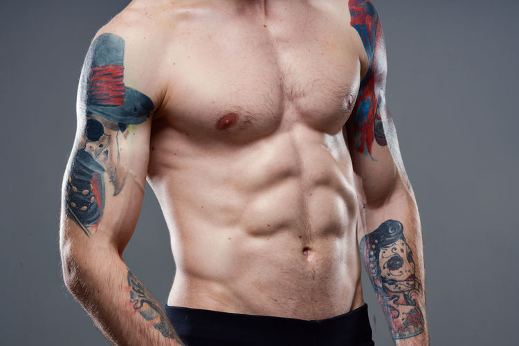 Midsection of shirtless man wearing hat