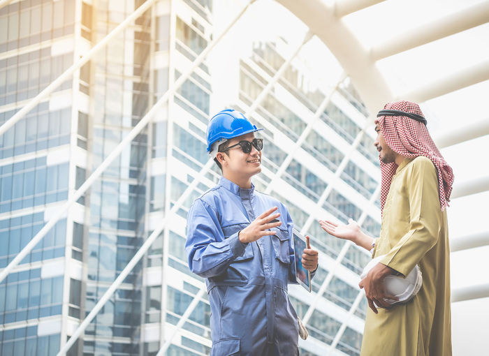 Arab architects and blue helmet engineers are consulting on joint projects. Architecture Building Exterior Built Structure City Communication Day Friendship Headwear Lifestyles Men Outdoors People Real People Technology Togetherness Two People Well-dressed Wireless Technology Young Adult Young Women