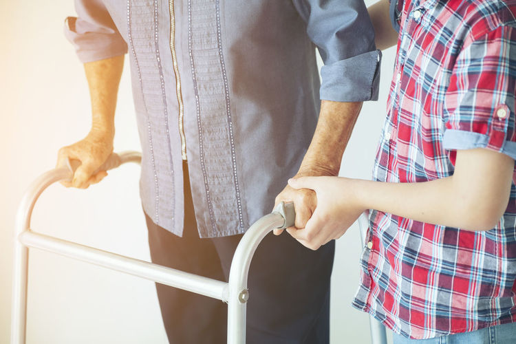 Midsection Of Boy Helping Senior Man With Mobility Walker