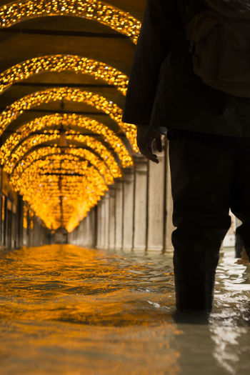 Low section of man standing in illuminated water at night