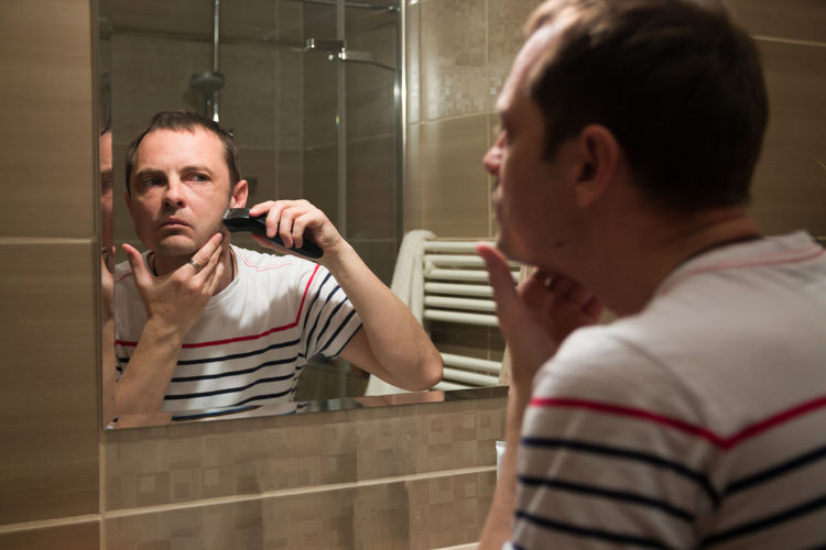 Reflection of man shaving in mirror at home
