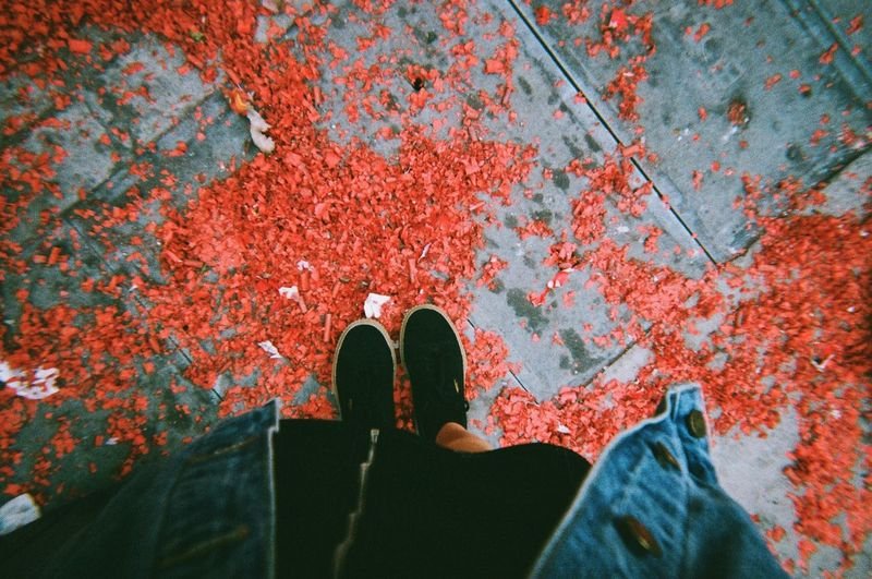 Low section of person standing by red shoes