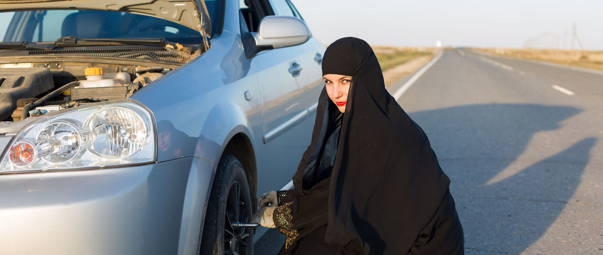 Portrait of woman in burka replacing tire on road