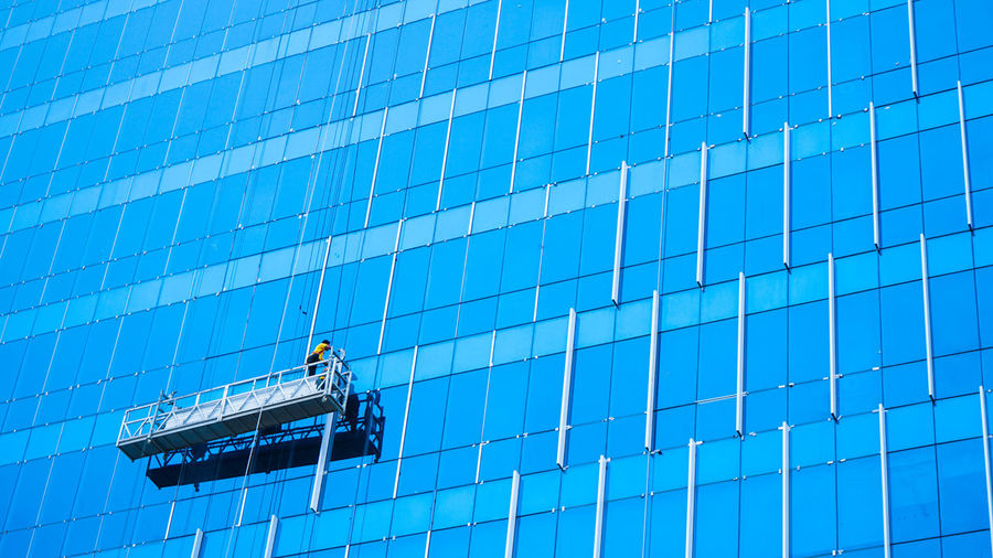 Low angle view of worker cleaning building windows