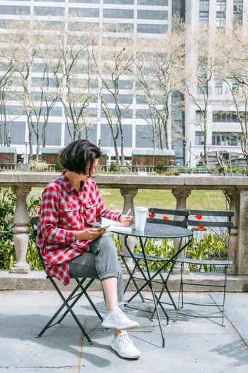 Young hipster woman texting message on cellphone and making notes innotebook working outside in park