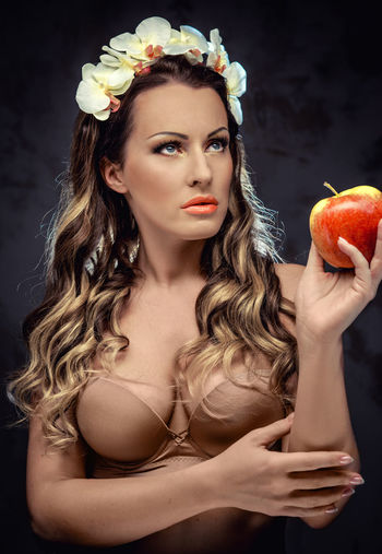 Sensuous Woman Looking Away While Holding Apple
