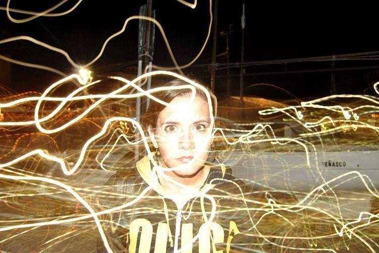 Portrait of woman with illuminated lighting equipment at night