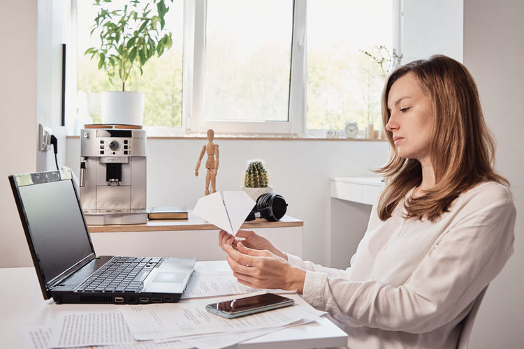 Woman using phone while sitting on table