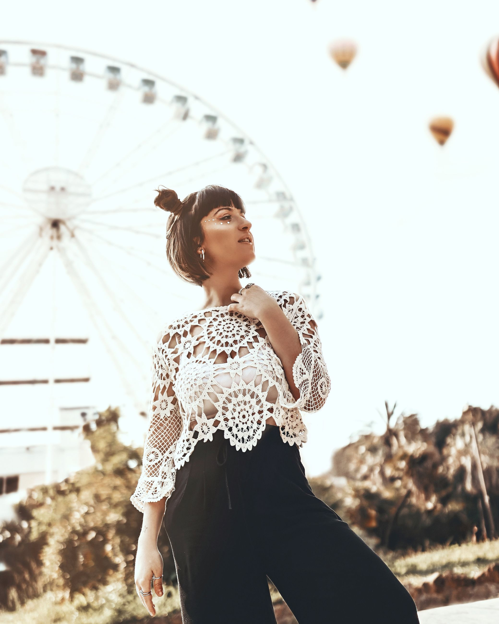 leisure activity, real people, amusement park ride, focus on foreground, one person, young adult, three quarter length, lifestyles, amusement park, ferris wheel, casual clothing, young women, front view, looking, nature, sky, women, standing, outdoors, beautiful woman, hairstyle