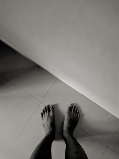 Low section of woman standing on tiled floor at home