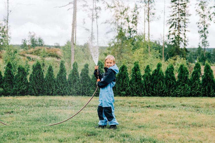 Full length of boy standing on grass against trees