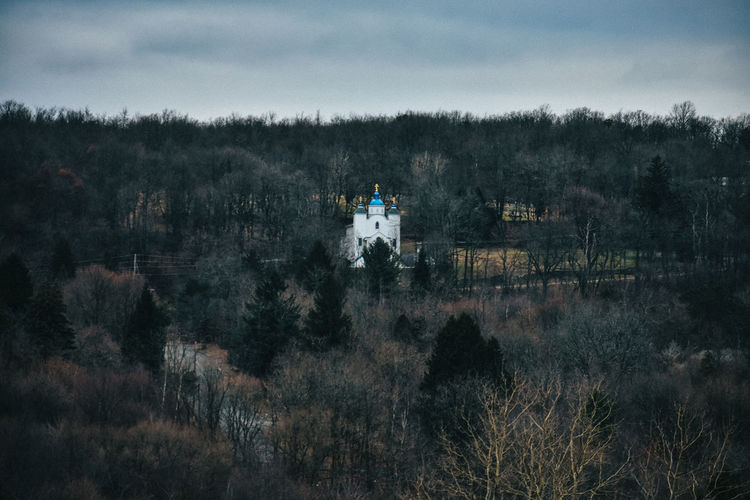 A lone church building with a blue roof on a mountain covered in dead trees with a cloudy sky