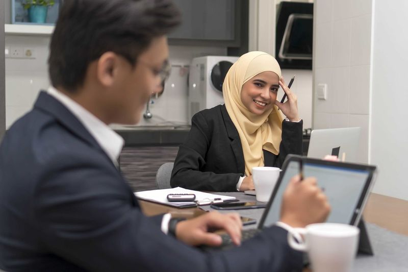 Asian malay muslim wearing hijab working at home with laptop with colleague at foreground Technology Adult Young Adult Wireless Technology Real People Communication Two People Connection Occupation Holding Business Headshot Indoors  People Young Women Portrait Men Women Office